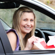 Jolly young female driver tearing up her L sign — Stockfoto