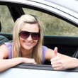 Happy female driver wearing sunglasses with thumb up — Stock Photo