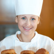 Charming young chef baking scones — Stock Photo