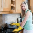 Stock Photo: Smiling young woman cleaning in a kitchen