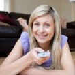 Jolly woman watching TV lying on the floor — Stock Photo