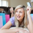 Joyful woman holding a credit card after shopping — Stock Photo