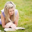 Beautiful woman reading a book in a park — Stock fotografie