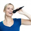 Happy girl singing on a microphone — Stock Photo
