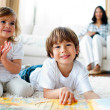 Jolly siblings eating chips and drawing - Stockfoto
