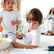 Adorable children eating chips and drawing — Stock Photo