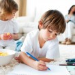 Happy children eating chips and drawing - Stock Photo