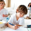 Cute little gir eating chips and her brother drawing — Stock Photo