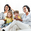 Excited little boy watching TV with his family — Stock Photo