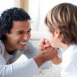 Cheerful father and his son armwrestling — Stock Photo #10297435