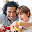Excited little boy and his father playing video games lying on t — Stock Photo