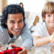 Cheerful father and his son playing video games lying on the flo — Stock Photo