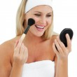 Blond woman putting on make-up — Stock Photo