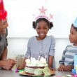 Smiling little girl and her family celebrating her birthday - Foto Stock