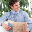 Stock Photo: Relaxed businessmreading newspaper