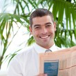 Attractive businessman reading a newspaper in workplace - Stock Photo