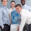 Busines standing around water cooler — Stockfoto