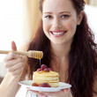 Smiling woman eating pancakes with fruit and honey — Stock Photo