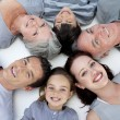 Happy family lying on floor with heads together — Stock Photo
