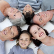 High angle of family lying on floor with heads together - Foto Stock