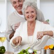 Happy senior couple eeating a salad in the kitchen — Stock Photo #10297913