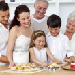 Parents and granparents looking at children baking - Foto Stock