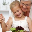 Happy grandmother cooking a salad with granddaughter — Stock Photo
