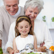 Happy grandparents eating a salad with granddaughter — Stock Photo
