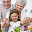 Smiling grandparents eating salad with granddaughter — Foto Stock #10297928