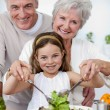 Smiling grandparents eating a salad with granddaughter — Stock Photo