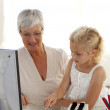 Little girl explaining her grandmother how to use a computer — Stock Photo