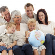 Big family on sofa looking at a terrestrial globe — Stok fotoğraf