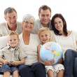 Big family on sofa holding a terrestrial globe - Foto Stock