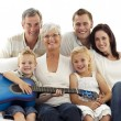 Stock Photo: Portrait of family playing guitar at home