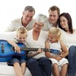 Happy family playing guitar at home - Foto Stock