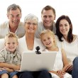 Happy family using a laptop at home - Foto Stock