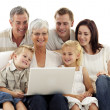 Happy family using a laptop in living-room - Foto Stock