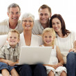 Smiling family using a laptop at home — Stock Photo