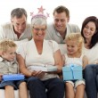 Family giving a gift to grandmother for her birthday — Stock Photo