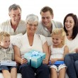 Family giving a gift to grandmother — Stock Photo