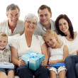 Stock Photo: Family giving a present to grandmother