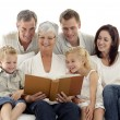 Grandmother reading a book to her family — Stock Photo