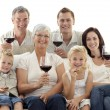 Family in living-room drinking wine and eating biscuits — Stock Photo