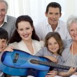 Stock Photo: Portrait of family holding a guitar in living-room