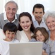 Portrait of family sitting on sofa using a laptop — Stock Photo