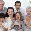 Family singing karaoke at home — Stock Photo