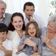 Family singing karaoke in living-room — Stock Photo
