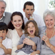 Happy family singing karaoke in living-room — Stock Photo