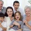 Happy family singing karaoke in living-room — Stock Photo #10298037