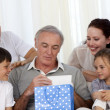 Family giving to grandfather a present — Stock Photo